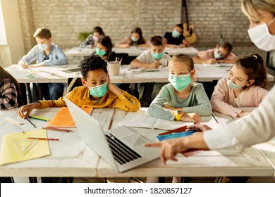 Group of school kids with protective face masks learning on laptop with their teacher during a class in the classroom.