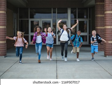 Group of school kids running as they leave the school building Back to school photo of a diverse group of children wearing backpacks and ready to go home from school