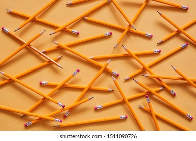 A group of school pencils has fallen on a yellow surface, haphazardly arranged on top of each other