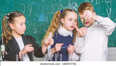 Group school pupils study chemical liquids. Test tubes with colorful substances. Girls and boy student conduct school experiment with liquids. Check result. School chemistry lesson. School laboratory.
