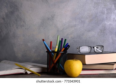 Group of school supplies and books on wooden table over a grey background