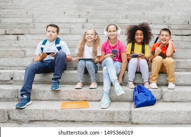 Group of schoolchildren in colorful clothes are sitting on the steps and looking at gadgets. Five classmates of different nationalities.