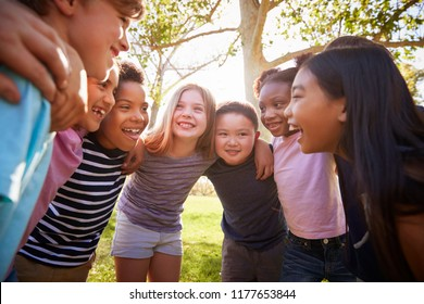 Group of schoolchildren embrace standing in a circle