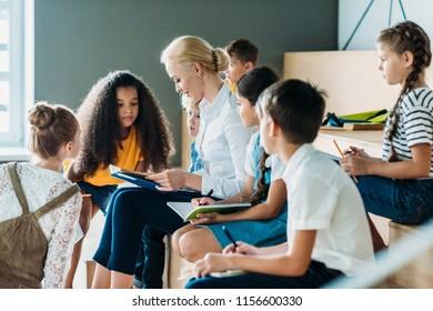 group of schoolchildren listening to their teacher while sitting on tribune