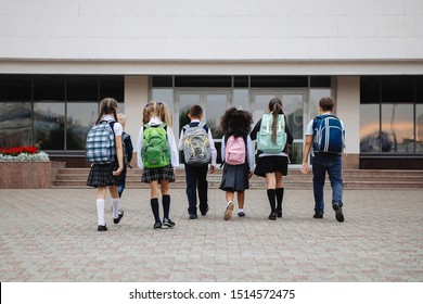 Group of schoolchildren in uniform with colorful backpacks are standing in a line in front of the school. Back view.