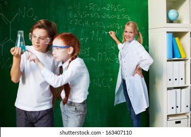 Group of schoolchildren working at chemistry lesson