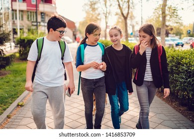 Group of schoolmates going home after school on sunny day and having fun
