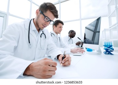 group of scientists sitting at the laboratory table