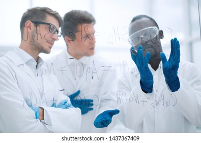 group of scientists talking standing near a glass Board.