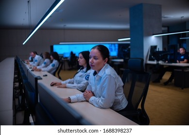 Group of Security data center operators (administrators) working in a group at a CCTV monitoring room while looking at multiple monitors ( computer screens)
