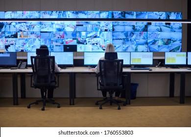 Gruppe von Betreibern von Sicherheitsdatencenter, die in einem CCTV-Überwachungsraum arbeiten und mehrere Monitore überwachen Team-Mitarbeiter, die an der Systemsteuerung arbeiten