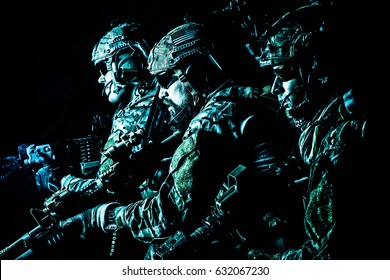 Group of security forces in Combat Uniforms with rifles, lined in the face of danger. Facing enemy, they stand boldly and ready to protect the nation. Studio contour silhouette shot, backlight
