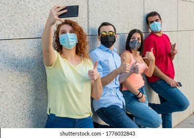 group selfie, young girls and boys in a row leaning against a wall take pictures with protective masks, concept of using prevention rules adapted to the sociality of young people