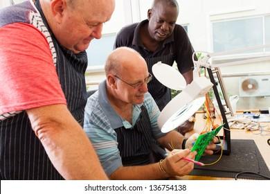 group of senior casual electrical technicians examining a circuit board