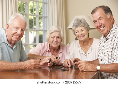 Group Of Senior Couples Enjoying Game Of Dominoes At Home