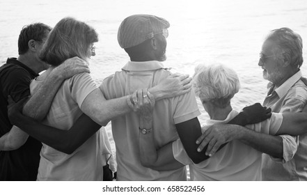 Group of senior friends arm around on the beach