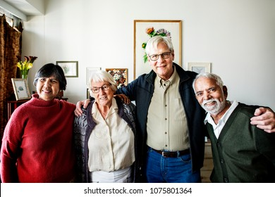 Group of senior friends arms around each other