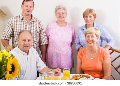 group of senior friends at breakfast table