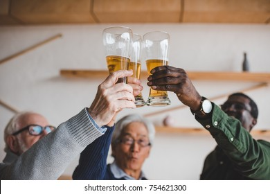 group of senior friends clinking glasses of beer at bar