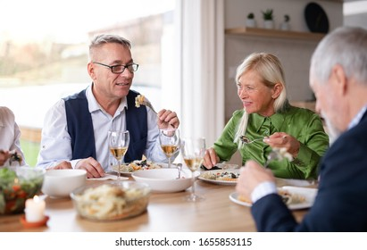 Group of senior friends at dinner party at home, eating.