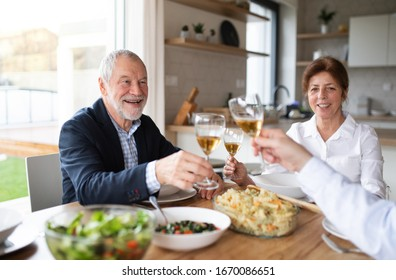 Group of senior friends at dinner party at home, clinking glasses.