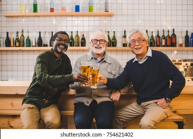 group of senior friends drinking beer together