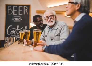 group of senior friends drinking beer together at modern bar