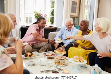 Group Of Senior Friends Enjoying Afternoon Tea At Home Together