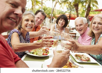 Group Of Senior Friends Enjoying Meal In Outdoor Restaurant