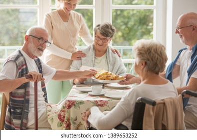 Group of senior friends with helpful carer sitting together at the table at nursing home dining room and eating cake