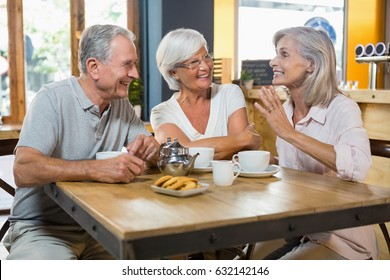 Group of senior friends interacting each other in cafe