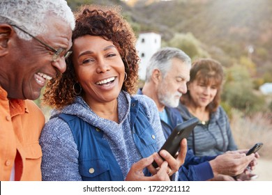Group Of Senior Friends On Hike In Countryside Looking At Mobiles Phones Together