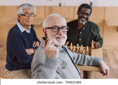 group of senior friends playing chess together and looking at camera