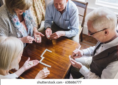 Group of senior friends are playing dominoes at a table together.