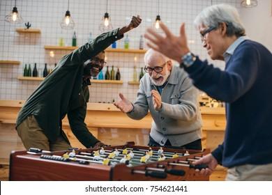 group of senior friends playing foosball at bar