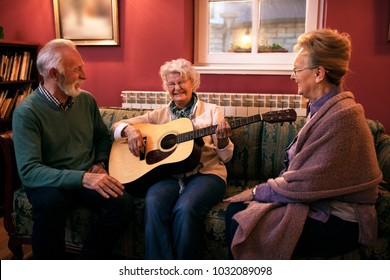 Group of senior friends playing guitar,singing and having fun at nursing home