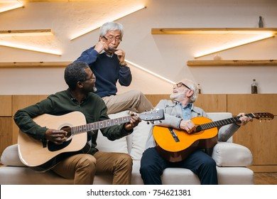 group of senior friends playing music with guitars and harmonica in modern public cafe