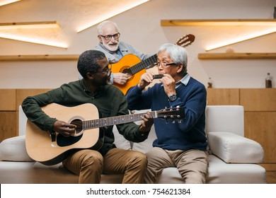 group of senior friends playing music together with guitars and harmonica