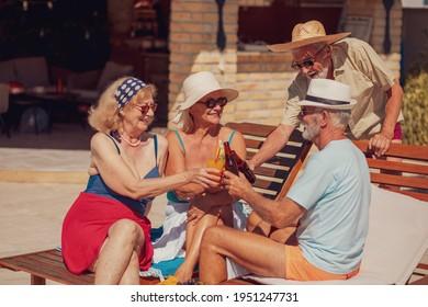 Gruppe von Senioren-Freunden entspannen und sonnen sich auf Liegestühlen am Pool während eines Sommerurlaubs, machen Toast, trinken Cocktails und Bier und Spaß