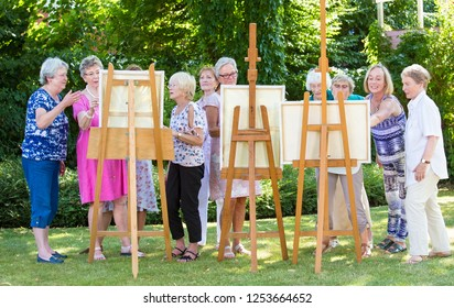 Group of senior ladies enjoying an art class outdoors in a park or garden as a therapeutic recreational activity at a care home.