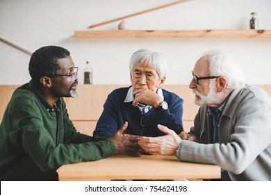 group of senior men having conversation in cafe