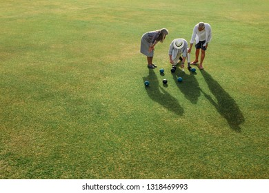 Group of senior people checking the distance between the boules and the jack to know the result of the game. Senior people playing a game of boules in a lawn.