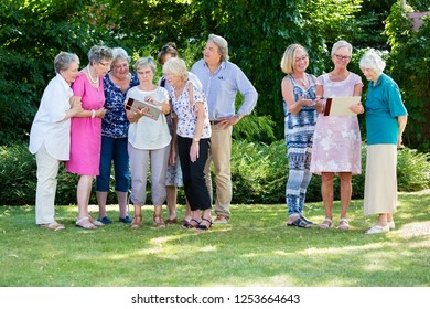 Group of senior people discussing their paintings together with course instructor, while standing in garden on sunny day.