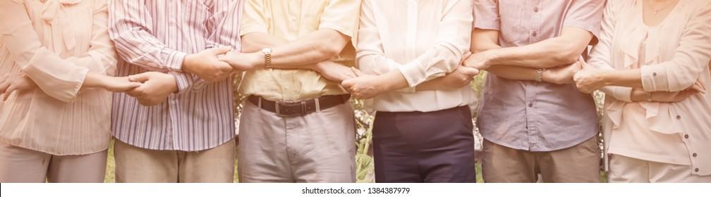 Group of senior people hands holding together in line, asian caucasian people work in pension house. Old people happy harmony retirement lifestyle concept panoramic banner.