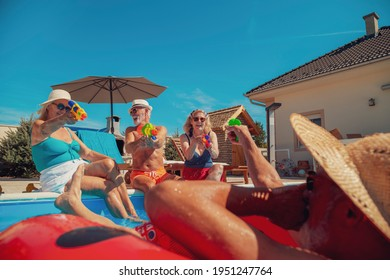 Group of senior people having fun spending hot sunny summer day at the swimming pool, playing with squirt guns, splashing water on each other