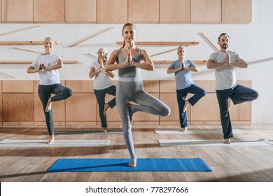group of senior people practicing yoga with instructor in tree pose on mats in studio