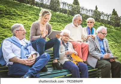 Group of senior people resting in a park - Mature friends doing some activities in a retirement home