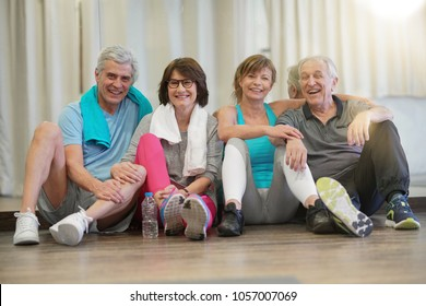Group of senior people sitting on floor in fitness room