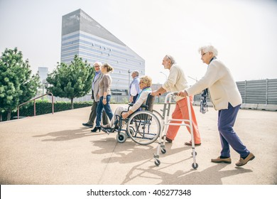Group of senior people with some diseases walking outdoors - Mature group of friends spending their time together in a almshouse