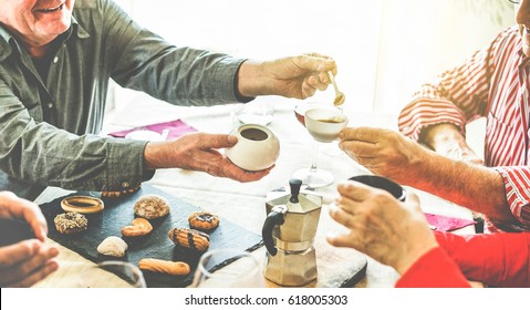 Group of senior people toasting italian style moka coffee after lunch - Mature happy friends eating biscuits and laughing together - Focus on men bottom hands - Warm contrast cine filter